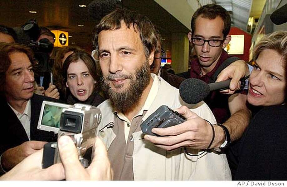 """Yusaf Islam, center, formerly known as the singer Cat Stevens arrives at London's Heathrow airport after being refused entry to America Thursday, Sept. 23, 2004. U.S. officials, who had ordered Islam taken off a London-to-Washington flight on Tuesday, said he was on a security watch list. """"I'm totally shocked,"""" Islam told a swarm of reporters as he came through the arrivals area at Heathrow airport. (AP Photo/David Dyson) ** UNITED KINGDOM OUT MAGS OUT ** Photo: DAVID DYSON"""