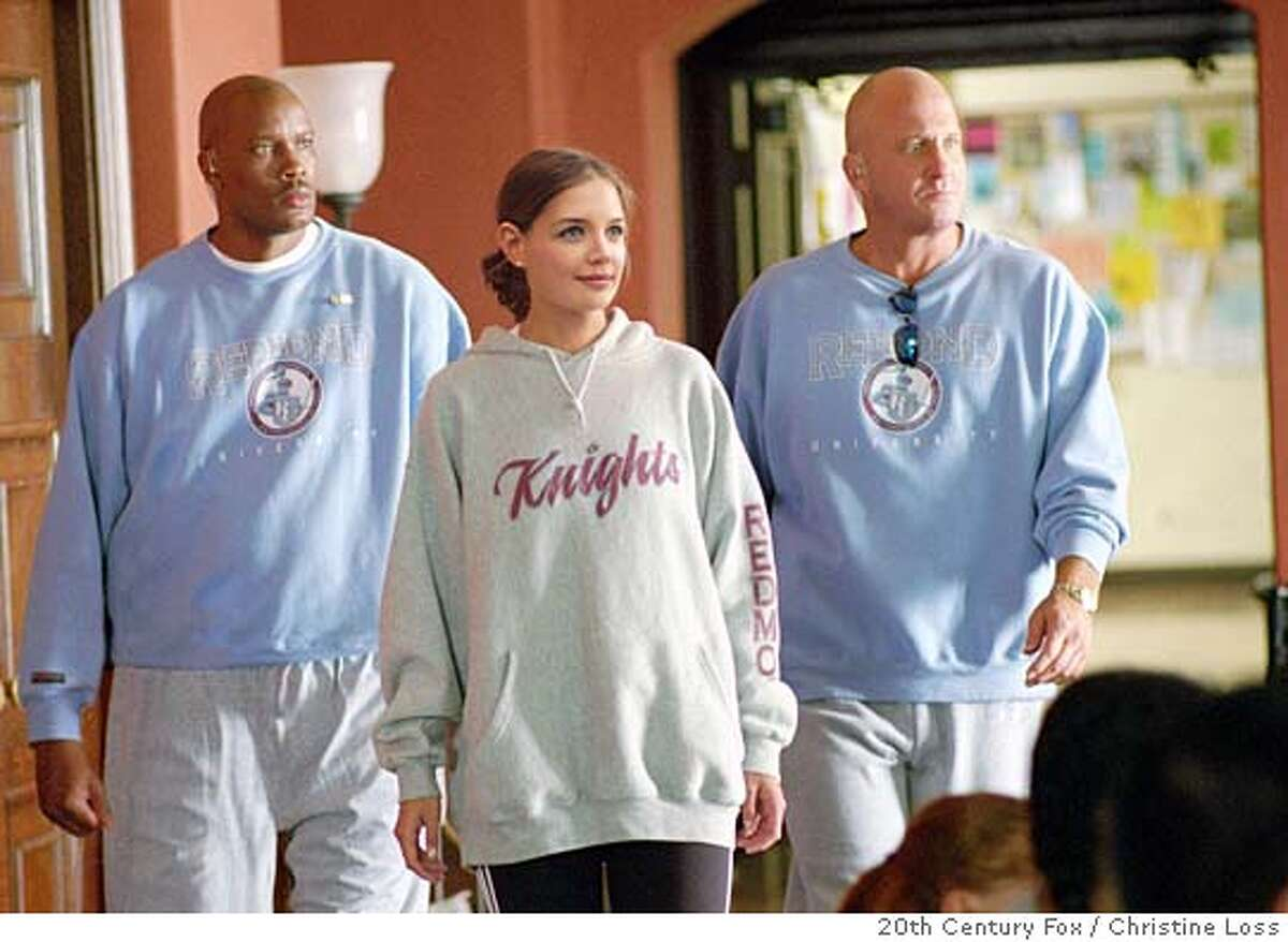 Katie Holmes, center, walks with her Secret Service detail Dwayne Adway, left, and Michael Milhoan, in this scene from the film
