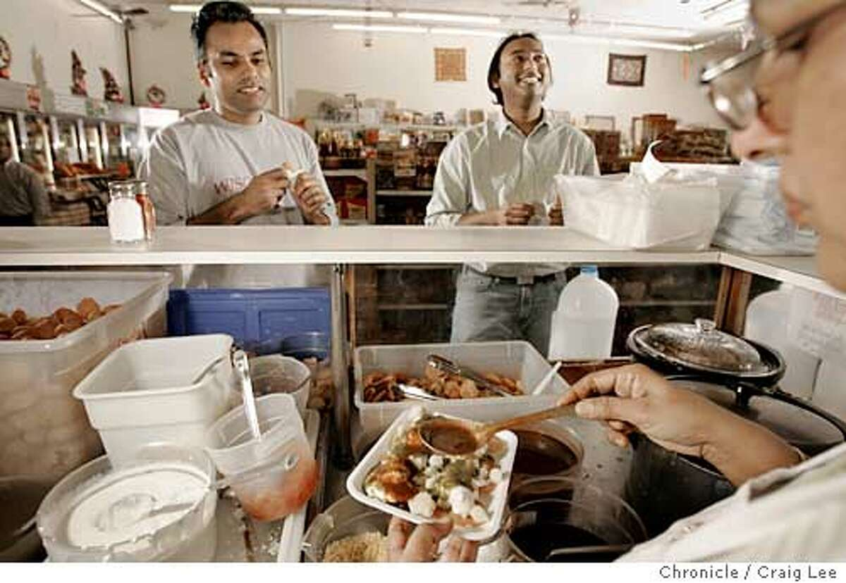 A food place in the corner of a grocery store. The food place is called Chatpatta Corner, the grocery store is called Dana Bazar, located in Fremont on 5113 Mowry Avenue. They serve an cuisine from India called chaat. Photo of Sunil Chandran (left) and Sebastian Jayaraj (right) at the counter, waiting for their chaat served by Sunit Sharma (far right). Event on 3/11/05 in San Francisco. Craig Lee / The Chronicle