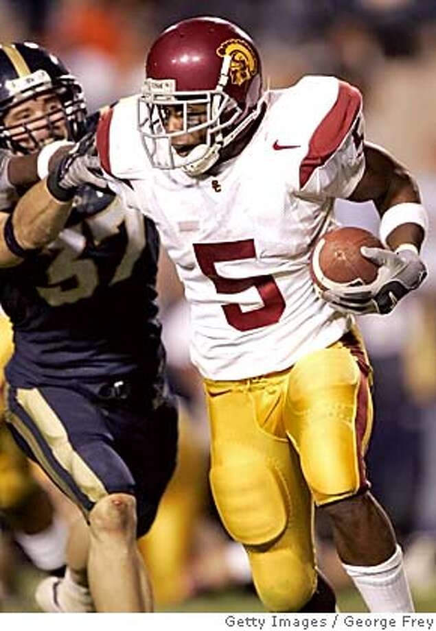 PROVO, UT - SEPTEMBER 18: Reggie Bush #5 of USC breaks the tackle of Jon Burbidge #37 of BYU and runs for a touchdown September 18, 2004 at Lavell Edwards Stadium in Provo, Utah. (Photo by George Frey/Getty Images) *** Local Caption *** Reggie Bush Sports#Sports#Chronicle#9/23/2004#ALL#5star##0422359482 Photo: George Frey