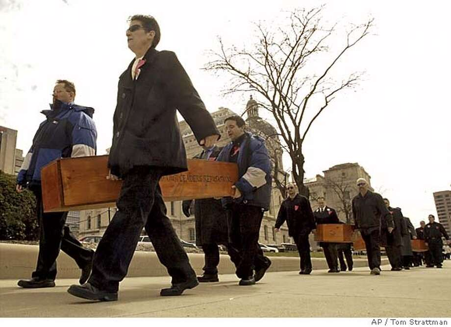 Tom Casbarro-Criss; Caroline Sitar; and Matthew Casbarro-Criss, from left, carry one of four coffins around the Statehouse in protest after a proposed constitutional amendment to ban gay marriage passed out of committee in Indianapolis Monday, March 14, 2005. (AP Photo/Tom Strattman) Photo: TOM STRATTMAN