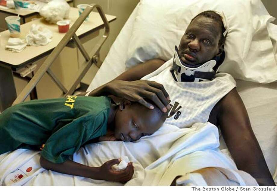 (NYT31) NEW BRITAIN, Conn. -- September 16, 2004 -- BKN-MANUTE-REHAB -- Rehabbing ex-NBA player Manute Bol caresses his son, Bol, at the Hospital for Special Care in New Britain, Conn., on September 8, 2004. Bol lines in a specially constructed bed to support his 7-foot-7-inch body, which was badly injured in a taxi cab accident June 30. (Stan Grossfeld/The Boston Globe) XNYZ Nation#MainNews#Chronicle#9/23/2004#ALL#5star##0422352943 Photo: STAN GROSSFELD