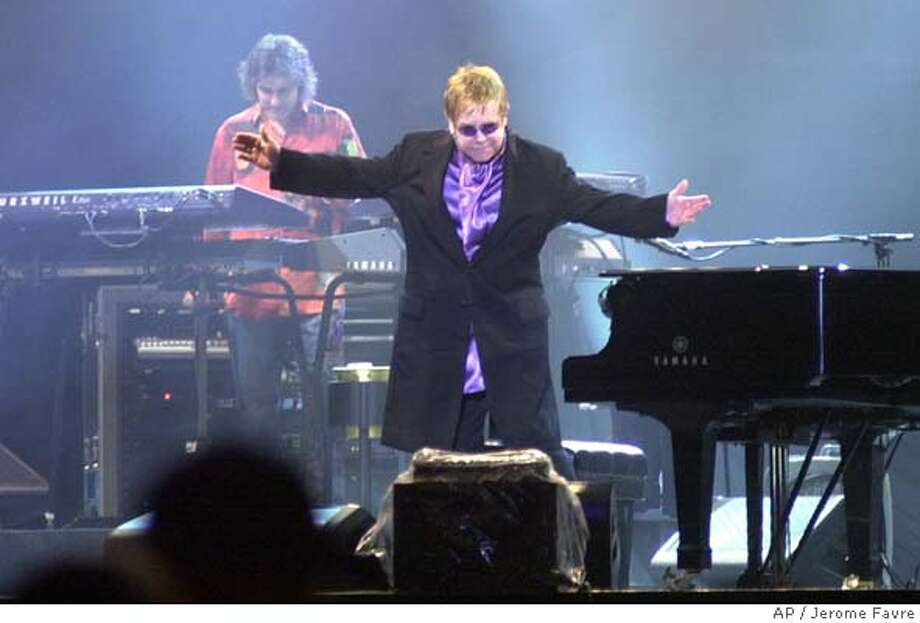 "British pop star Sir Elton John takes a bow during a concert in Taipei, Taiwan, part of his world tour, Thursday, Sept. 23, 2004. John got involved in a shouting match with local photographers and TV crews who swarmed around him at the airport on arrival and called them ""rude, vile pigs."" (AP Photo/Jerome Favre) Photo: JEROME FAVRE"