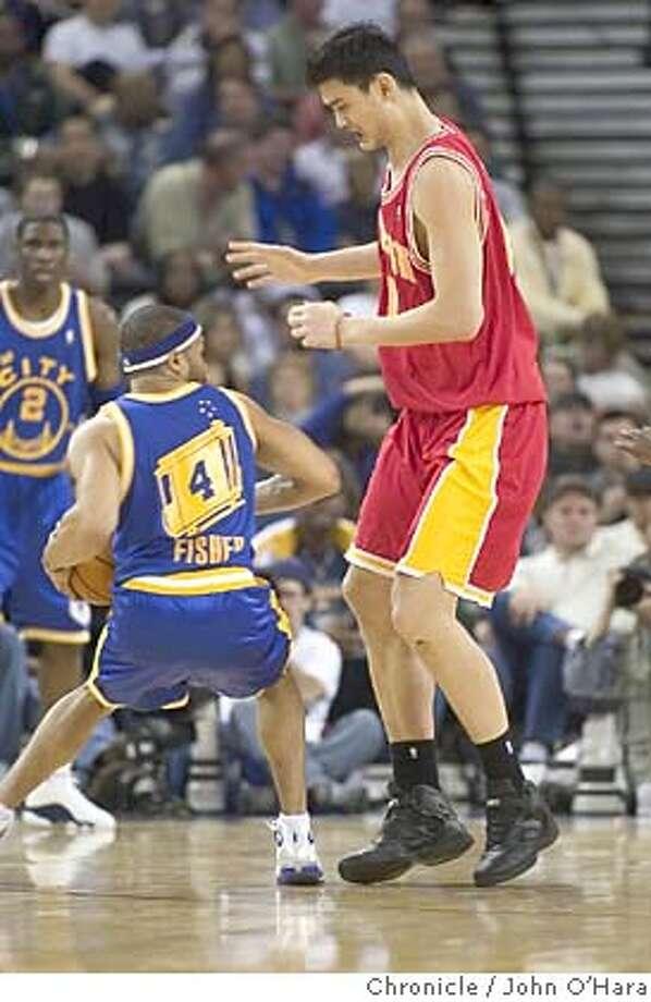 The Arena in Oakland.  Golden State Warriors V/S Houston Rockets  \Rockets Yao Ming, dwarfs Warriors #4 Derek Fisher  photo/ John O'Hara Photo: John O'Hara