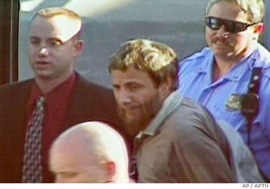 ** CORRECTS SPELLING OF YUSUF ** Yusuf Islam, center, formerly known as singer Cat Stevens, shown in this image from television, is surrounded by unidentified security personel as he departs an airplane at Dulles airport, Wednesday, Sept. 22, 2004, in Chantilly, Va. Islam was detained after a flight to the United States because his name is on a government anti-threat watch list. (AP PHOTO/APTN)