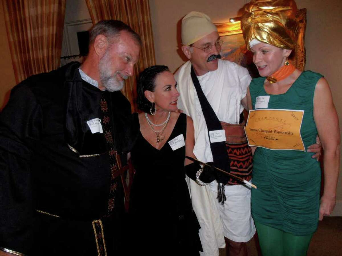 Sam and Annie Pack compare costumes with Dr. Fred and Sandi Goldner (dressed as Shandi and a Champagne bottle) at the Confrerie (accent on first e in Confrerie) de la Chaine des Rotisseurs (accent on the o in Rotisseurs) murder mystery party.