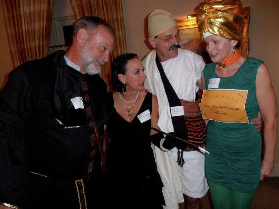 Sam and Annie Pack compare costumes with Dr. Fred and Sandi Goldner (dressed as Shandi and a Champagne bottle) at the Confrerie (accent on first e in Confrerie) de la Chaine des Rotisseurs (accent on the o in Rotisseurs) murder mystery party. / Photo by Nancy Cook-Monroe