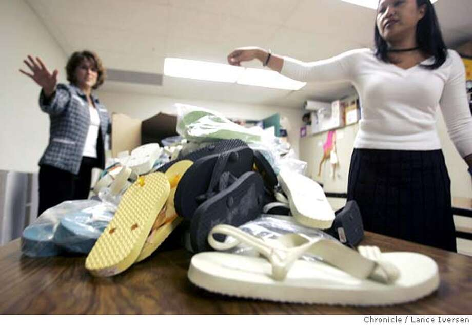 FLIPFLOPSTWO_0008_LI.JPG Jo Loecher Leadership teacher at Danville's Charlotte Wood Middle School shows off a few flipflops to Denise Castanea from Wells Fargo Bank who donated money for transportation of the shoes to Iraq. By Lance Iversen/San Francisco Chronicle MANDATORY CREDIT FOR PHOTOG AND SF CHRONICLE/ -MAGS OUT-WIRES SERVICES OUT/GARY FONG Metro#Metro#Chronicle#9/23/2004#ALL#5star##0422368805 Photo: Lance Iversen