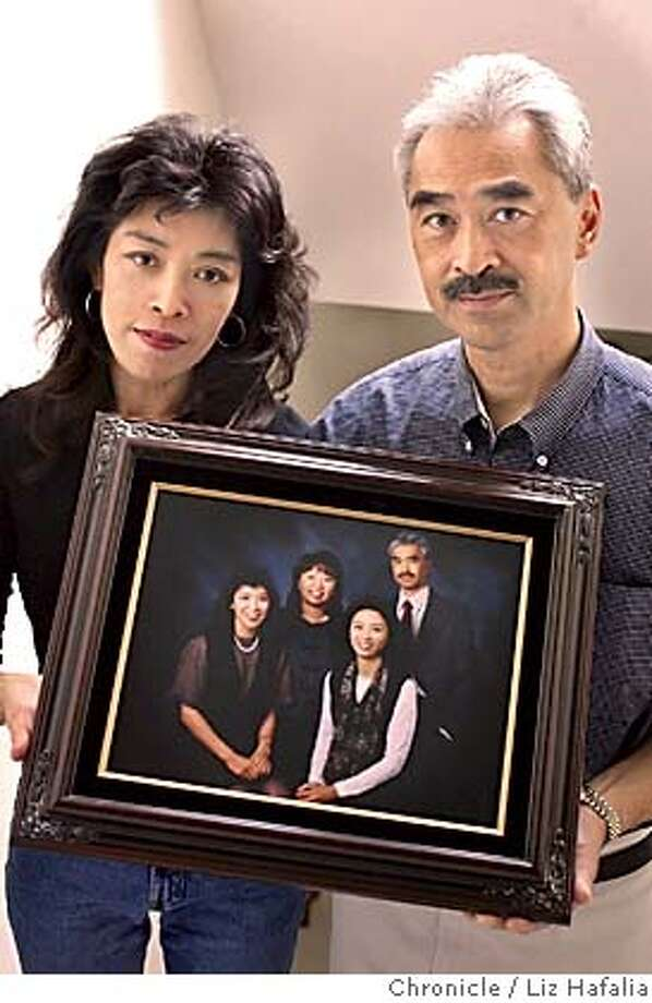 ONG22_019_LH.JPG Gloria Ong (left) and brother Harry Ong Jr. (right) holding a picture of their sisters/brother. From left to right on picture--Gloria Ong, Cathie Ong-Herrera, Betty Ong (with white shirt), and Harry Ong Jr. Shot on 9/21/04 in San Francisco. LIZ HAFALIA / The Chronicle Photo: LIZ HAFALIA
