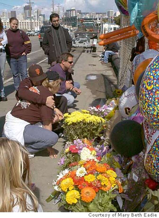 stabbing002.JPG  Foreground: Stacey Redman (Tim's mother), Joshua Griffith (Tim's brother) holding Redman, Josh Griffith (Tim's father) at the memorial for Tim Griffith, who was stabbed to death after attending a Giants game. Behind are friends. The memorial is on the spot where Griffith died, on Terry Francois Bl. just south of SBC Park. PHotos Courtesy of Mary Beth Eadie