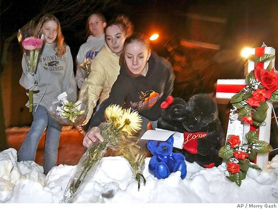Chelsey Porth, left to right, Kaitlin Schaeren, Ariel Reuter and Kelly Rooney all of New Berlin, Wis., leave flowers outside the Sheraton Hotel Saturday, March 12, 2005, in Brookfield, Wis. A gunman opened fire Saturday at a church service being held at the hotel, killing at least eight people and wounding several others, police said. The gunman then apparently shot and killed himself, Brookfield Police Chief Daniel Tushaus said. (AP Photo/Morry Gash) Photo: MORRY GASH