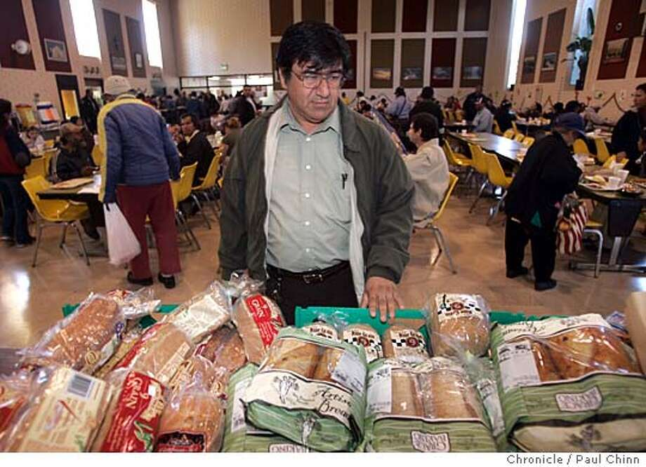 Max Torres looks over the mountain of bread products donated by the community for the needy his organization serves. Jefferson Award winner Maximiliano Torres at the St. Anthony's Padua Dining Room on 12/22/04 in Menlo Park, CA. Torres began as a volunteer in 1982 and now oversees the non-profit operation that serves 600 meals a day, six days a week.  PAUL CHINN/The Chronicle Photo: PAUL CHINN