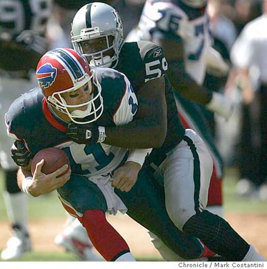 RAIDERS Linebacker DeLawrence Grant(59) grins as he sacks Bills QB Drew Bledsoe IN THE FIRST HALF.  THE RAIDERS V.BUFFALO BILLS AT THE NETWORK COLISEUM.  EVENT ON 9/19/04 IN OAKLAND.  S.F. Chronicle Photo: Mark Costantini Photo: Mark Costantini