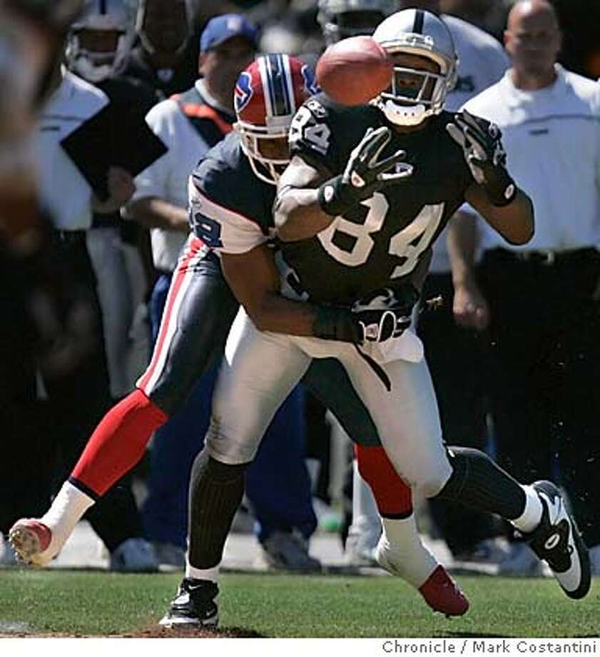 Raiders Wide Receiver Jerry Porter reaches for a pass as bills Cornerback Nate Clements covers on the play.  IN THE FIRST half..  THE RAIDERS V.BUFFALO BILLS AT THE NETWORK COLISEUM.  EVENT ON 9/19/04 IN OAKLAND.  S.F. Chronicle Photo: Mark Costantini Photo: Mark Costantini