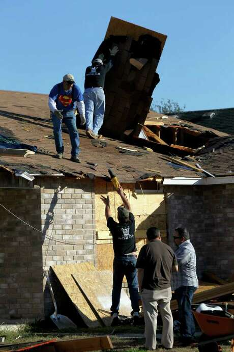 Workers for R&A Restoration Contractors start clean up efforts Thursday at a home on the 8900 block of Deer Park where a tornado touched down early Wednesday morning damaging nine homes in the area. Photo: John Davenport, San Antonio Express-News