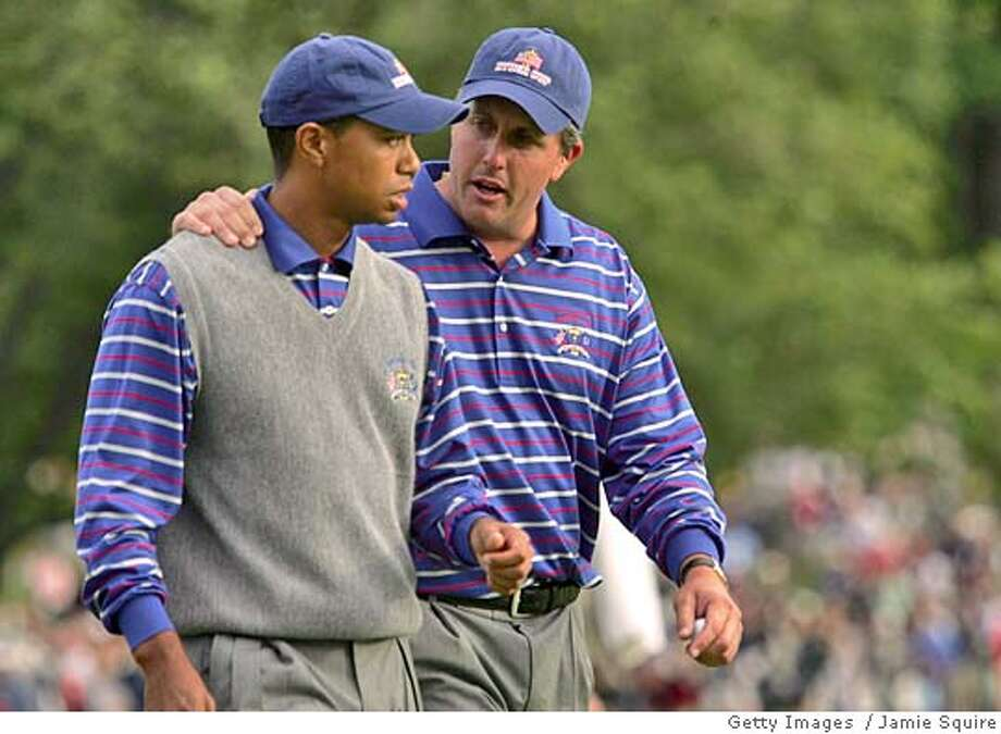 BLOOMFIELD TOWNSHIP, MI - SEPTEMBER 17: USA team players Tiger Woods and Phil Mickelson walk off the 18th green during their afternoon foursome match against Darren Clarke and Lee Westwood of Europe at the 35th Ryder Cup Matches at the Oakland Hills Country Club on September 17, 2004 in Bloomfield Township, Michigan.. (Photo by Jamie Squire/Getty Images) *** Local Caption *** Tiger Woods; Phil Mickelson Ran on: 09-18-2004  Phil Mickelson (right) and Tiger Woods walk off the 18th green after their second loss of the day. Photo: Jamie Squire