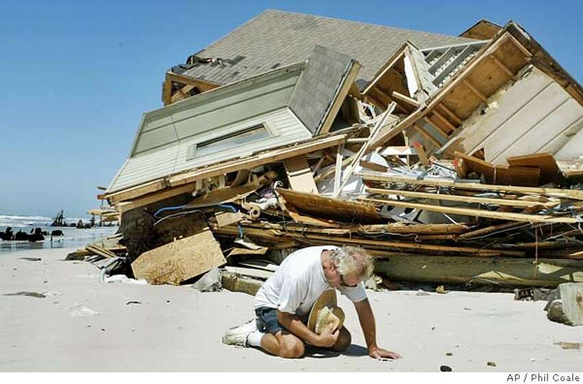 The owner of this house on Cape San Blas kneels to pray in front of the rubble, Friday, Sept. 17, 2004, in Cape San Blas, Fla. The home was destroyed by the winds and waves of Hurricane Ivan as it passed through the area on Wednesday night. When asked if he would rebuild in the same location, he stated that he was insured and would take the money and do good with it, whatever that might be. (AP Photo/Phil Coale) Ran on: 09-18-2004 The owner of this house in Cape San Blas, Fla., crumpled by Ivans wind and waves, kneels helplessly in front of the rubble. Ran on: 09-18-2004 The owner of this house in Cape San Blas, Fla., crumpled by Ivans wind and waves, kneels helplessly in front of the rubble.