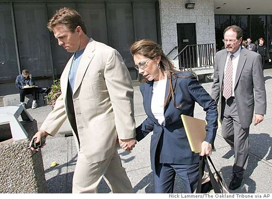Former Oakland Raiders linebacker Bill Romanowski exits Alameda County Superior Courthouse with his wife Julie, Tuesday, March 8, 2005, in Oakland, California where he is on trial for punching teammate Marcus Williams and breaking his eye socket. (AP Photo/Nick Lammers/The Oakland Tribune) Photo: NICK LAMMERS