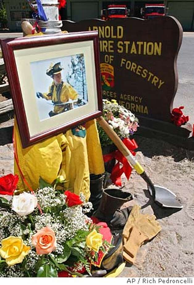 A photograph of California Department of Forestry firefighter Eva Schicke tops a memorial setup in her honor in front of the CDF's Arnold Forest Fire Station, in Arnold, Calif., Monday, Sept. 13, 2004. Schicke, 24, of Arnold, was killed Sunday after she and six other firefighters were dropped into rugged terrain just outside Yosemite National Park and overrun by the flames. Her body was recovered Monday morning. Her six crew members were released after being treated for injuries they suffered while trying to cut off the fire's advance through the Tuolumne River Canyon. (AP Photo/Rich Pedroncelli) Photo: RICH PEDRONCELLI