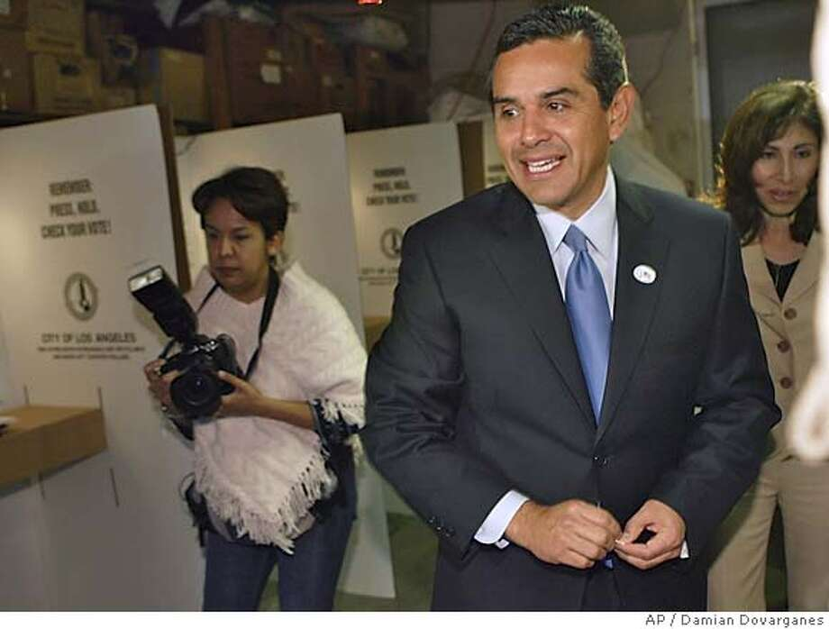 Los Angeles mayoral candidate Antonio Villaraigosa joins his wife Corina, right, as she casts her vote Tuesday, March 8, 2005, in the Mount Washington section of Los Angeles. Villaraigosa had already voted earlier absentee. (AP Photo/Damian Dovarganes) Photo: DAMIAN DOVARGANES