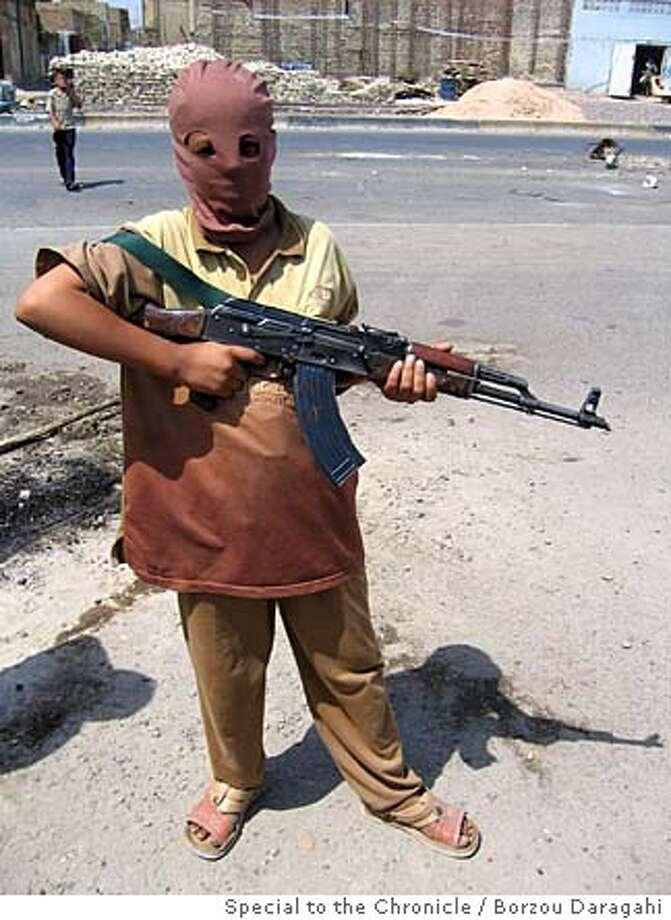 Ibrahim, armed with a Kalashnikov, patrols the streets of Sadr City for rebellious cleric Muqtada al-Sadr. Photo by Borzou Daragahi, special to the Chronicle