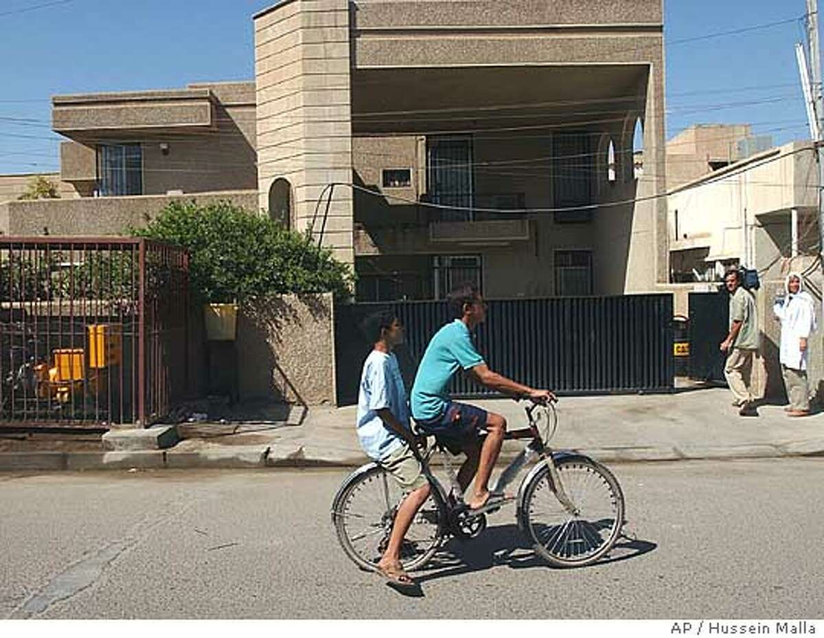 Children of neighbors take a bicycle ride outside the house in al-Mansour, Baghdad, Iraq, from which gunmen abducted two Americans and a Briton on Thursday Sept. 16, 2004. The three were employed by Gulf Services Company, a Middle East-based construction firm. (AP Photo/Hussein Malla)