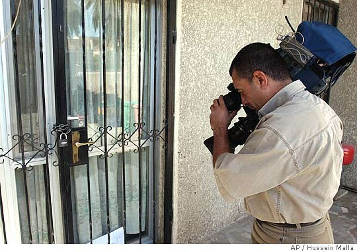 A cameraman films at the house in al-Mansour, Baghdad, Iraq, from which gunmen abducted two Americans and a Briton on Thursday Sept. 16, 2004. The three were employed by Gulf Services Company, a Middle East-based construction firm. (AP Photo/Hussein Malla)