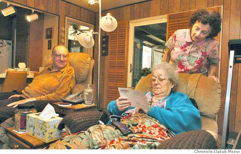 Homeowners Frank Reed, 80, and Adele Reed, 79, and renter Laura Adair, 71 wearing the pink shirt, read some mail at their home in Belmont on Tuesday, August 18, 2004. Adair provides some cooking and cleaning and other services instead of actually having to pay rent. on 8/17/04 in Belmont. JAKUB MOSUR / The Chronicle Photo: JAKUB MOSUR