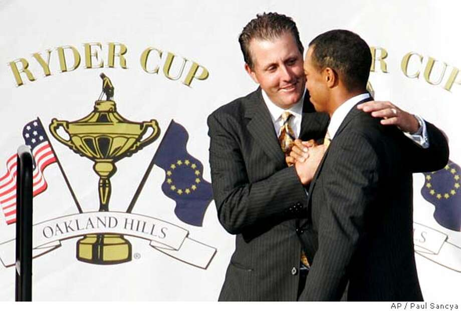 U.S Ryder Cup team members Phil Mickelson and Tiger Woods shake hands on stage during the opening ceremonies for the 35th Ryder Cup matches at Oakland Hills Country Club in Bloomfield Township, Mich., on Thursday, Sept. 16, 2004. Mickelson and Woods will be teamed together Friday morning in a four-ball match. (AP Photo/Paul Sancya) Photo: PAUL SANCYA