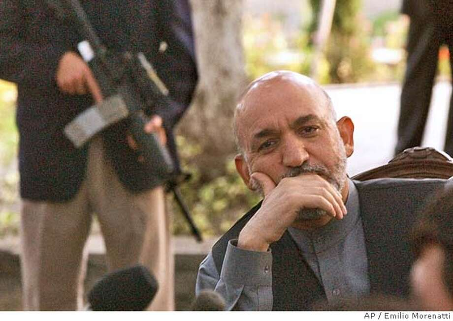 Afghan President Hamid Karzai listens to a reporter's question during a press conference in Kabul, Afghanistan, Tuesday, Sept. 14, 2004. Karzai escaped a rocket attack on the U.S. helicopter carrying him to a provincial capital in eastern Afghanistan Thursday, Sept. 16, 2004, officials said. No one was hurt. (AP Photo/Emilio Morenatti) Photo: EMILIO MORENATTI