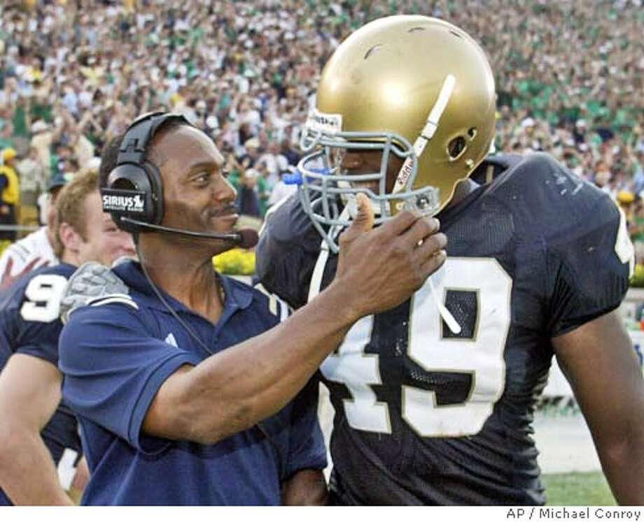 Notre Dame coach Tyrone Willingham, left, and linebacker Derek Curry hug as they walk off the field following a 28-20 win over Michigan in South Bend, Ind., Saturday, Sept. 11, 2004. (AP Photo/Michael Conroy) Photo: MICHAEL CONROY