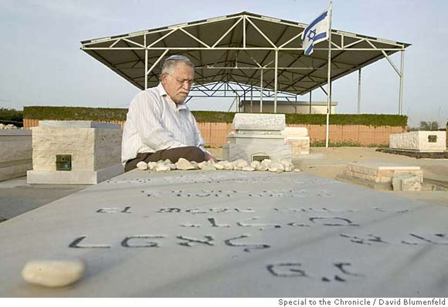 2004-03-01-Gush Katif Cemetery, Gaza: Shlomo Yulis, 66, places a stone (a Jewish tradition) on the grave of his son, Etai, who passed away from Leukemia several years ago. Part of the Gaza Disengagement Plan includes moving the Jewish Cemetery to another location.  �David Blumenfeld