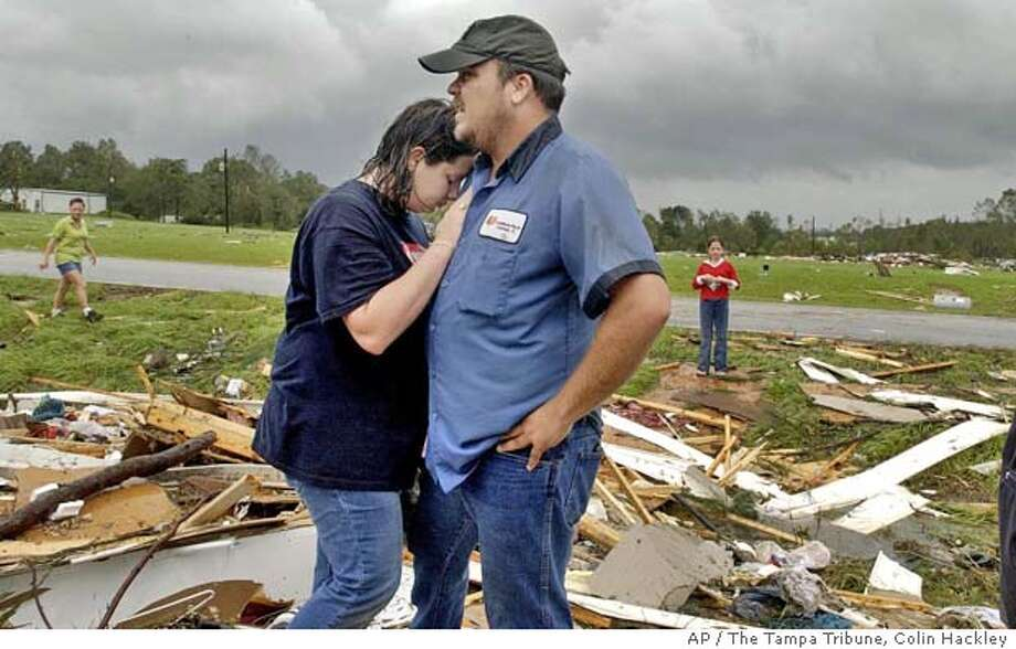 Santana Sullivan, 19, left, leans against her fiance, Chris Ammons, as they look at the remains of their mobile home in the aftermath of Hurricane Ivan, Thursday, Sept. 16, 2004, near Blountstown, Fla. The couple heeded the warnings of relatives and left their home before a tornado struck. They are to be married in two weeks. (AP Photo/The Tampa Tribune, Colin Hackley) OUT BRADENTON, LAKELAND, ST.PETE, WINTER HAVEN, NO MAGS Photo: COLIN HACKLEY