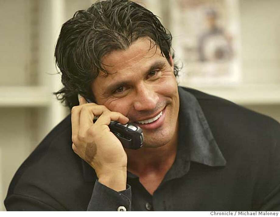 CANSECO08_015_MJM.jpg  Jose Canseco talks to former teammate Rickey Henderson on a cell phone given to him by Henderson's mother-in-law Rosalind Ono of Oakland. She was first in line to meet Canseco and handed him the phone.  Baseball star Jose Canseco hawks his new book 'Juiced : Wild Times, Rampant 'Roids, Smash Hits, and How Baseball Got Big' at Barnes and Noble in Oakland. A few hundred fans stood in line for hours to meet the former A's player.  Photo by Michael Maloney / San Francisco Chronicle MANDATORY CREDIT FOR PHOTOG AND SF CHRONICLE/ -MAGS OUT Photo: Michael Maloney