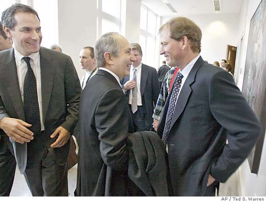Former University of Washington head football coach Rick Neuheisel, right, smiles as he greets John Aslin, center, who was the lead attorney for the NCAA, as Neuheisel's lead attorney Bob Sulkin looks on at left, outside a King County Superior Courtroom in Kent, Wash. Monday, March 7, 2005, shortly after it was announced that all parties had reached a settlement in Neuheisel's lawsuit against the NCAA and the UW over his 2003 firing. Neuheisel won $4.7 million in the settlement, with $2.5 million coming from the NCAA and $2.2 million coming from the UW. (AP Photo/Ted S. Warren) Photo: TED S. WARREN