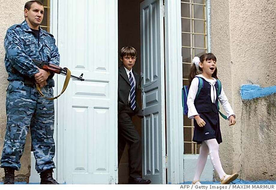 An Ossetian police officer stands guard outside school No. 6 in Beslan, North Ossetia, 15 September 2004, as schools in the town reopened after the hostage crisis. Students returned to school in Beslan for the first time since hundreds of children and their parents were killed in a violent end to a mass hostage-taking at a Beslan primary school. AFP PHOTO / MAXIM MARMUR (Photo credit should read MAXIM MARMUR/AFP/Getty Images) Photo: MAXIM MARMUR