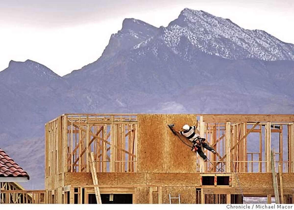 """Construction in Northern Las Vegas almost to the edge of the mountains that define the city. KB Homes project, """"Iron Mountain"""" sub-division. Last year the City of Las Vegas grew it's home price growth by an amazing 52% in the region. placing it atop the all time U.S. rankings for annual real estate appreciation and far ahead of the Bay Area's 17%. But in recent months, other economic measures paint a more sobering picture, where the growth may be ebbing. One new home builder in the area, reduced prices on its units last fall by about $100,00. In December , existing home sales declined nearly 11% and more homes languished on the market. 2/10/05 Las Vegas, Nv Michael Macor / San Francisco Chronicle"""