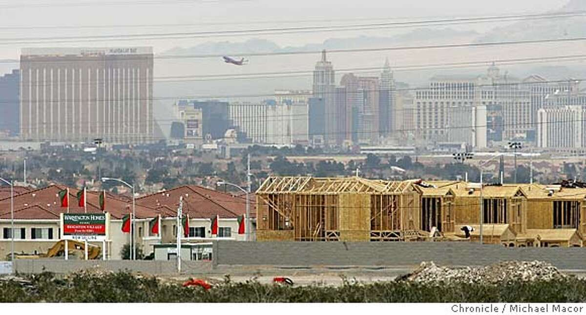 """vegas_157_mac.jpg Construction pushing the Southern edge of Las Vegas, with this developement going up with the skyline of '""""The Strip"""" in the background. A Warmington Homes housing project. Last year the City of Las Vegas grew it's home price growth by an amazing 52% in the region. placing it atop the all time U.S. rankings for annual real estate appreciation and far ahead of the Bay Area's 17%. But in recent months, other economic measures paint a more sobering picture, where the growth may be ebbing. One new home builder in the area, reduced prices on its units last fall by about $100,00. In December , existing home sales declined nearly 11% and more homes languished on the market. 2/10/05 Las Vegas, Nv Michael Macor / San Francisco Chronicle Mandatory Credit for Photographer and San Francisco Chronicle/ - Magazine Out"""