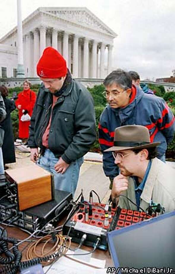 Neal Becton of Washington, left, Prasad Kadambi of Silver Spring, Md., and Rev. Gregory Apelian, right, of Rio Rancho, N.M., listen to the recording of the U.S. Supreme Court hearing near the high court in Washington, Friday Dec. 1, 2000, after lawyers for Republican Ppresidential candidate Texas Gov. George W. Bush and Democratic presidential candidate Vice President Al Gore pleaded their cases before Supreme Court justices, openly questioning whether they should intervene in the nations contested presidential election. For the first time, the justices released an audio tape of the argument shortly after it ended. (AP Photo/Michael DiBari Jr.) Photo: MICHAEL DIBARI JR.