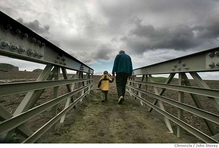 {object name}  Sasha Jacimovic of San Francisco walks over a bridge to get to the beach with his grandson, Marco Jacimovic, 3, at Rodeo Beach in Sausalito. Weather pictures in Marin and San Francisco. John Storey San Francisco Event on 3/4/05 MANDATORY CREDIT FOR PHOTOG AND SF CHRONICLE/ -MAGS OUT Photo: John Storey