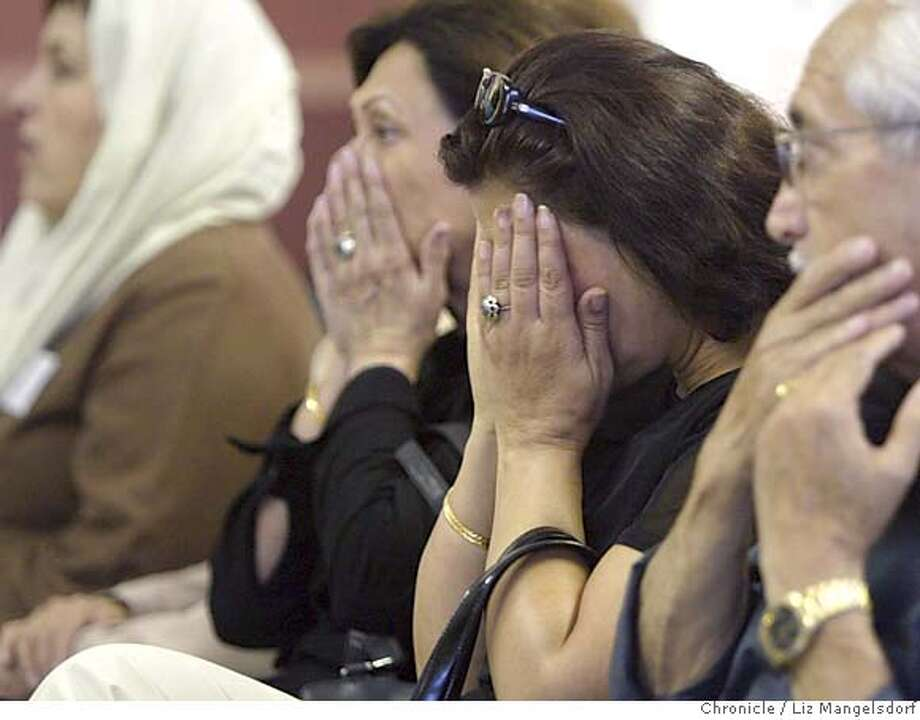 Event on 9/11/04 in Fremont.  Halima Ahmed, second from right, covers her face at the end of a prayer during the rememberance for the victims of Sept. 11th. She was there with her husband Aziz Ahmed, blurred right. Both are resients of Fremont, but were born in Afghanistan. A prayer and rememberance of September 11 is held at the Mohammadia Mosque in Fremont sponsored by the Afghan Coalition. Speakers included members of the Muslim and Afghan bay area community, as well as Fremont community leaders from city government and local christian churches. The memorial was held to show support for victims and families of Sept. 11th, as well as to show support for the fight against terrorism. Liz Mangelsdorf / The Chronicle Photo: Liz Mangelsdorf