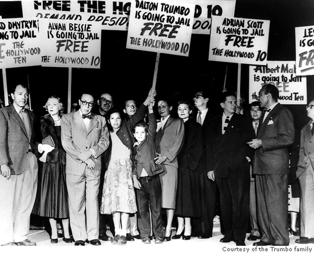 DALTON03 Pictured: Dalton Trumbo (third from left, in glasses) prepares to fly to Washington D.C. to begin serving his jail sentence, as his children Nicky and Christopher (holding sign) and wife Cleo (right of Christopher) join a group protesting the jailing of the Hollywood Ten � Los Angeles Airport, 1950.� Photo Credit: Courtesy of the Trumbo family