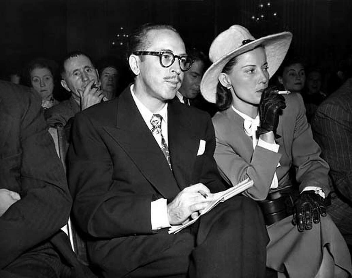 Screenwriter Dalton Trumbo, left, and his wife, Cleo, listen from the audience as the chairman of the House Un-American Activities Committee (HUAC) announces a contempt citation against Trumbo at a hearing in Washington, D.C., Oct. 28, 1947. On the witness stand Trumbo, one of the Hollywood Ten called before the committee, declined to say whether he is or has been a Communist. Trumbo served a prison sentence in 1950 and was blacklisted in the film industry. (AP Photo)