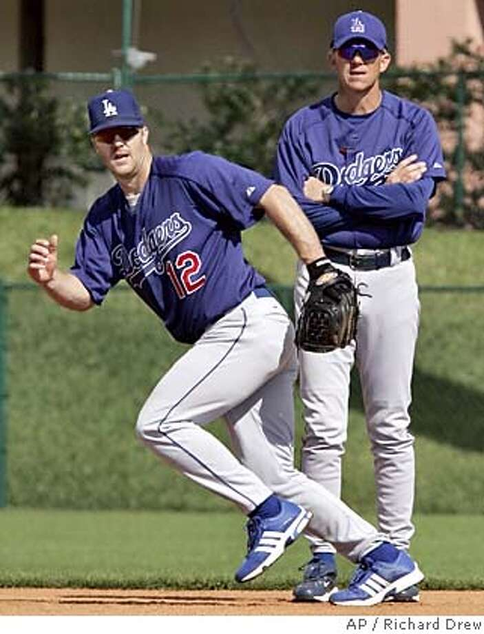 Los Angeles Dodgers second baseman Jeff Kent, left, chases down a ball as manager Jim Tracy looks on at Holman Stadium during spring training workouts at Dodgertown in Vero Beach, Fla., Saturday Feb. 26, 2005. (AP Photo/Richard Drew) Photo: RICHARD DREW
