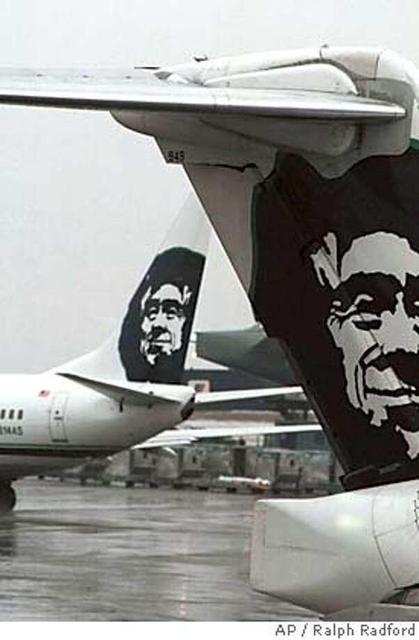 FILE--An Alaska Airlines MD-80 sits at Seatac Airport in Seattle on Tuesday, Feb. 1, 2000, as another Alaska Airlines plane leaves. The Federal Aviation Administration proposed Friday, June 2, 2000, to strip Alaska Airlines of the right to perform maintenance on its planes, a step that could eventually force the airline to park its planes and stop flying. The airline has seven days to respond, showing steps it has taken to avoid losing its maintenance authority.(AP Photo/Ralph Radford) ALSO RAN 10/19/2001 CAT Photo: RALPH RADFORD