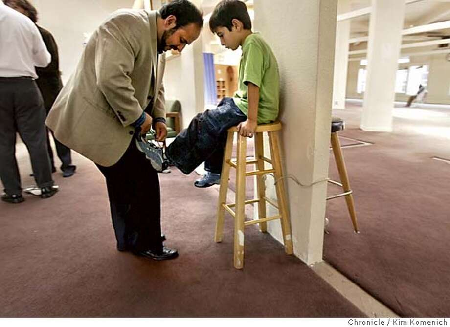 Islamic Society of San Francisco President Souleimaan Ghali ties the shoes of his son Ibrahim, 6, after Friday prayers.  First assignment on story about Bay Area Muslims. We visit the Islamic Society of San Francisco Mosque at 20 Jones St.  Photo by Kim Komenich in San Francisco Photo: Kim Komenich