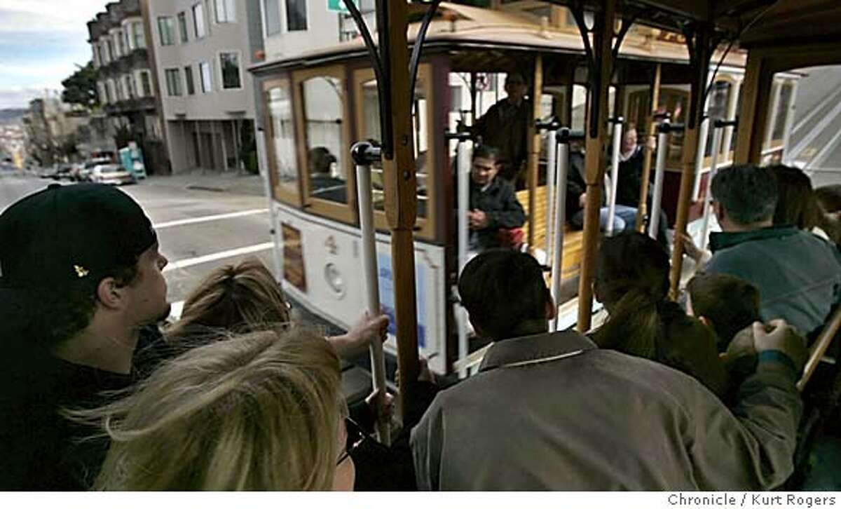 Riders on the powell st cable car line pass another car going the opposite way. It is mostly tourists riding in the afternoon. Among the proposals being pushed by Muni officials to close its $57 million deficit is a 60 percent increase in cable car fares, from the current $3 to $5. But will the little cable cars climb 80 percent of the way to the stars instead of halfway to the stars? And will the tourists continue to sit still for being gouged? MUNI_CABLE02_0151_kr.JPG 3/1/05 in San Francisco,CA. KURT ROGERS/THE CHRONICLE MANDATORY CREDIT FOR PHOTOG AND SF CHRONICLE/ -MAGS OUT