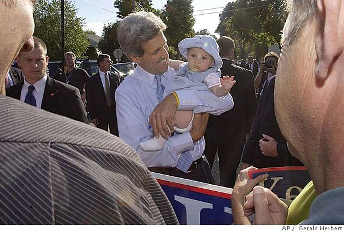 Democratic presidential nominee Sen. John Kerry, D-Mass, holds a baby after speaking at a front porch campaign stop in Rochester, Minn. Wednesday, Sept. 8, 2004. (AP Photo/Gerald Herbert) EDS: MARKS ON BABY'S FACE ARE DUE TO LENS FLARE