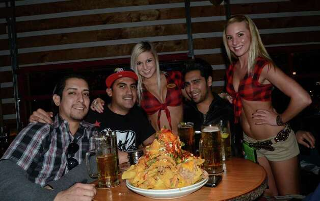 Estevban Alvarado (cq) (from left), Saul Contreras and Vincent Lopez get ready to face Twin Peaks' monster nachos with their waiteresses Jessica Beam (left) and Mere Davis (right) on January 21, 2012. Robin Johnson
