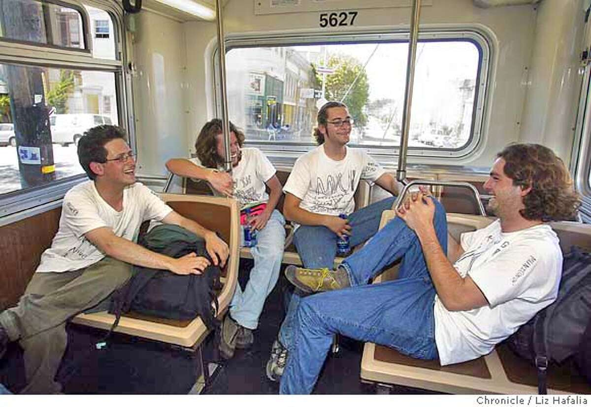 left top right--Zhenya Warshavsky, Nate Maas, Gil Hackel, and Trammell Scruggs talk and play games while catching bus 21 to the Ferry building. These four college students are planning to ride every single MUNI line in San Francisco from start to finsh over the Labor Day weekend. Shot on 9/5/04 in San Francisco. LIZ HAFALIA / The Chronicle